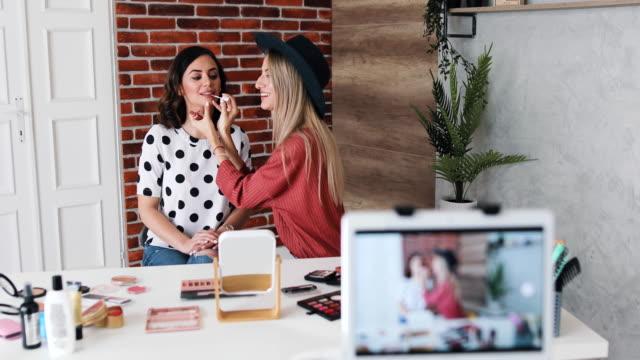 video von zwei fröhlichen jungen frauen sitzen in einem aufnahmestudio und eine von ihnen ist auf der anderen aufmachung make-up auf andere, während sie spaß beim filmen eines video-tutorial für ihr internet-und social-media-publikum haben. - kosmetik beratung stock-videos und b-roll-filmmaterial