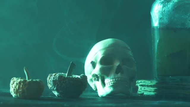 vídeos y material grabado en eventos de stock de video 4k de dos calabazas, botella venenosa y cráneo humano para el concepto de halloween - halloween covid