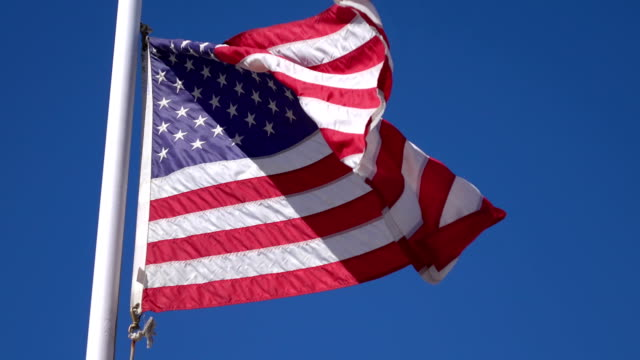 Video of United States flag waving in the wind in 4K video