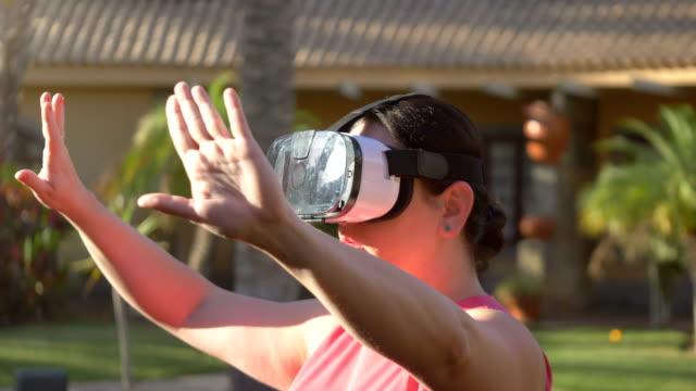 Video of woman exploring virtual reality in tropical resort in 4k video