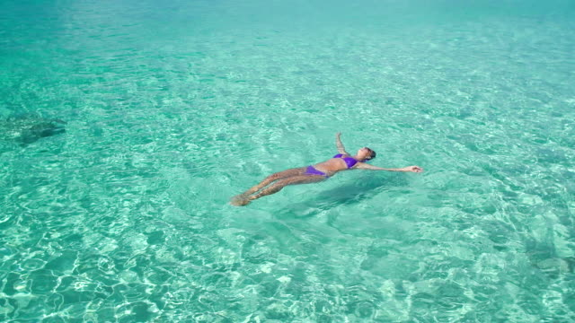video of woman floating on water at a Caribbean beach slow motion video of woman floating on water at a Caribbean beach shallow stock videos & royalty-free footage