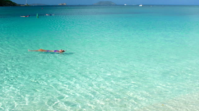 video of woman floating on water at a Caribbean beach video