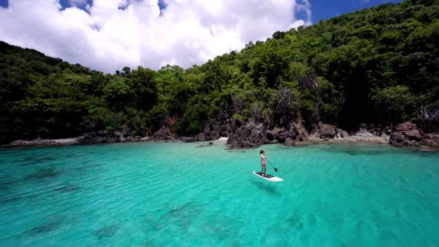 vídeos de stock, filmes e b-roll de vídeo de canoagem mulher em uma prancha de stand up paddle no caribe - remo esporte aquático