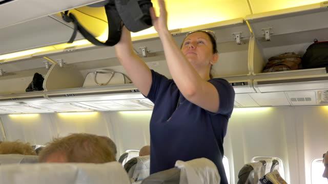 4 k에서 비행기 한 오버 헤드 오두막 짐을 씌우고 여자의 비디오 - airplane seat 스톡 비디오 및 b-롤 화면