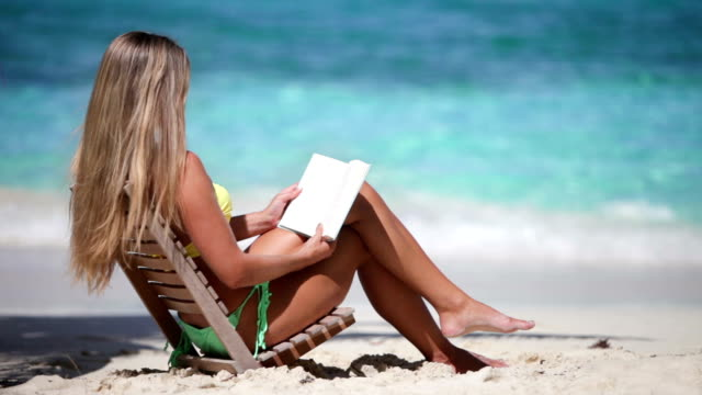 video of woman reading a book at the tropical beach video of a young woman in bikini sitting in a teak chair and reading a book at a tropical beach in the Virgin Islands cross legged stock videos & royalty-free footage