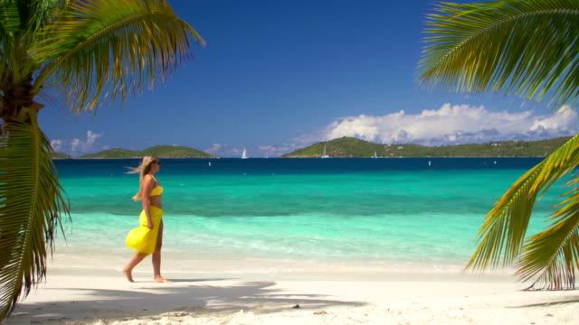 video of woman walking along the caribbean beach shoreline - sarong bildbanksvideor och videomaterial från bakom kulisserna
