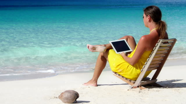 video of woman working on a tablet at the beach video