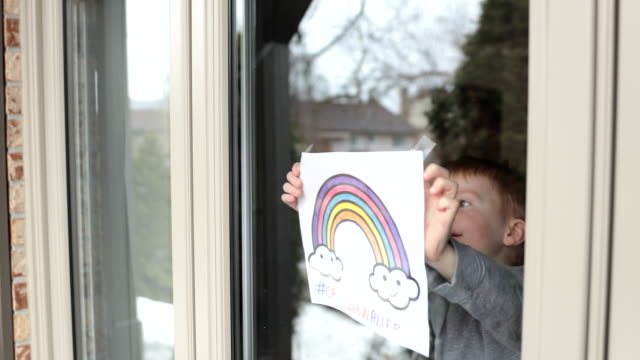 4K Video of Young Boy sticking his drawing on home window during the Covid-19 crisis