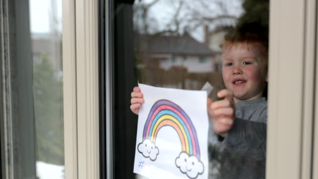 4k video of young boy sticking his drawing on home window during the covid-19 crisis - kids drawing стоковые видео и кадры b-roll