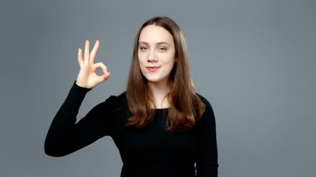 video of young girl in black shirt showing ok gesture - top nero video stock e b–roll