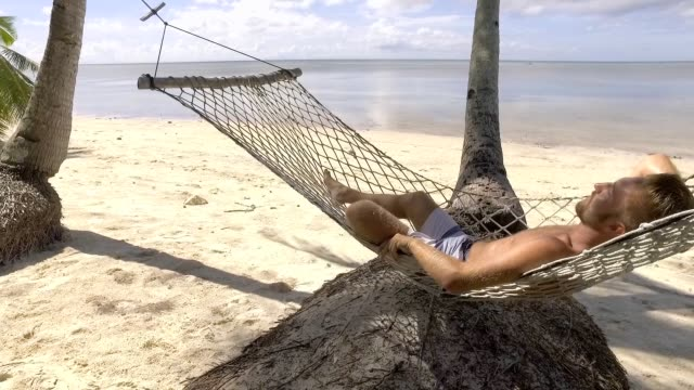 slow motion video of young man relaxing on hammock by the beach on tropical island in the philippines. people travel vacations relaxation concept. - amaca video stock e b–roll