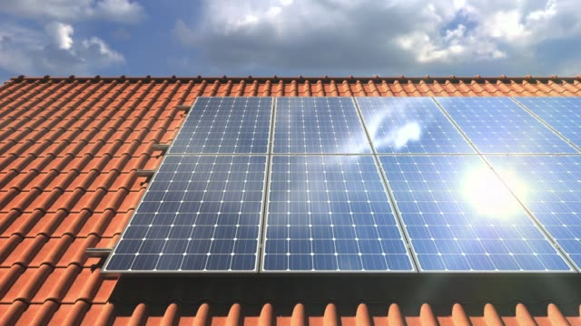 video panning of solar panels modules on roof on a sunny day - sustainability video stock e b–roll