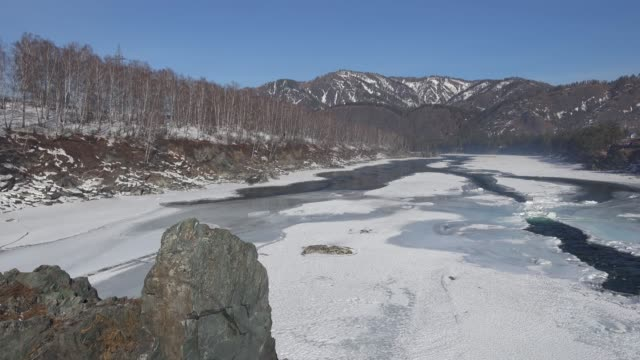 vídeos de stock e filmes b-roll de video panorama of altai river katun near elekmonar settlements with  floating of ice in water and mountains on background in winter season - sibéria