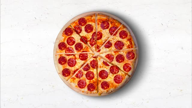 Video pepperoni pizza on a white marble kitchen table.