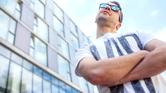 Video portrait of a confident man Young handsome caucasian man relaxing outside, having fun, standing and looking around charming stock videos & royalty-free footage