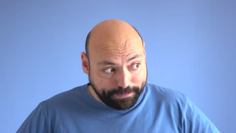 UHD Video Portrait Of Embarrassed Adult Man UHD 4K video portrait of adult man wearing a blue sweater doing embarrassment facial expression in front of blue colored background. He has beard and his head is bald. Shot in studio. facial expression stock videos & royalty-free footage