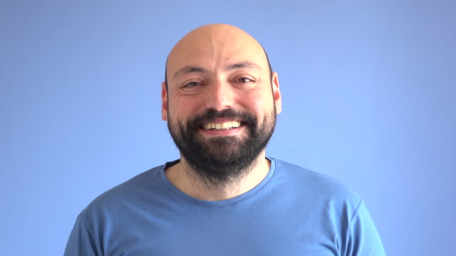 UHD Video Portrait Of Happy Smiling Adult Man UHD 4K video portrait of adult man wearing a blue sweater doing happiness facial expression in front of blue colored background. He has beard and his head is bald. Shot in studio. background color stock videos & royalty-free footage