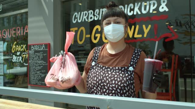 Video Portrait of Restaurant Proprietor Holding Takeout Order Outside Restaurant During Covid-19 Lockdown