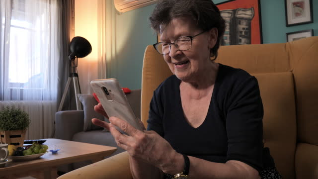 video portrait of senior woman at home using smart phone and watching images or movies - nonna video stock e b–roll