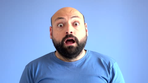 UHD Video Portrait Of Surprised Adult Man UHD 4K video portrait of adult man wearing a blue sweater doing surprised facial expression in front of blue colored background. He has beard and his head is bald. Shot in studio. facial expression stock videos & royalty-free footage