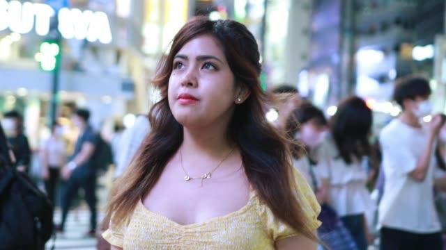 vidéos et rushes de verticale vidéo de jeune femme latine dans la nuit - carrefour
