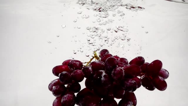 vídeos de stock e filmes b-roll de video red grapes in slow motion. bunch of ripe grapes are immersed in water with bubbles. - grapes