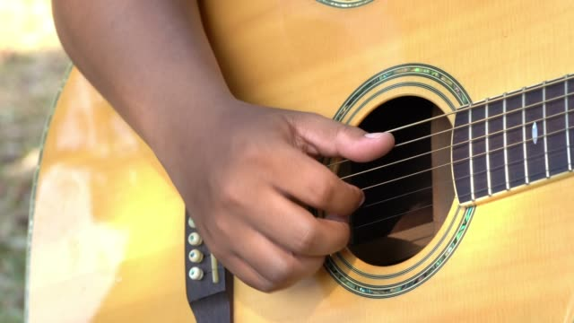 vídeos de stock, filmes e b-roll de vídeo 4k fim do foco seletivo acima do tiro da mão do homem novo que joga cordas de bronze de uma guitarra acústica. as mãos do músico novo jogam os acordes na guitarra. - música acústica