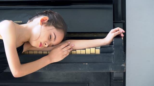 vidéos et rushes de 4k vidéo sélective focus moyen fermer dolly shot de jeune petite ballerine fille en justaucorps noir dormant seul dans la chambre sur le piano noir. - une seule petite fille