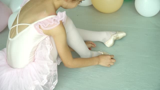 4k video selective focus medium close up shot side view of young  beautiful ballerina girl in pink leotard and tutu sitting on the floor and tie her ballet slipper shoe - tutù video stock e b–roll