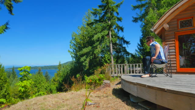 Video Summer Cabin view from Bluff, Man Walks and Sits in Chair video