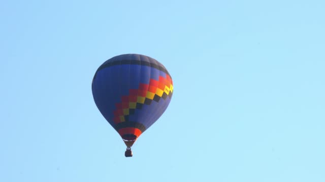 4K Video tracking shot of blue colorful single hot air balloons flying up in the air flight from left to right at spectacular white sky and green screen or chroma key background. Hot air balloons flying down in the air. hot air balloon stock videos & royalty-free footage