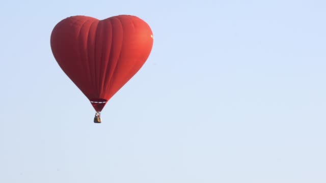 4K Video tracking shot of red color single heart shape hot air balloons flying up in the air flight at spectacular white sky and green screen or chroma key background. Hot air balloons flying down in the air. hot air balloon stock videos & royalty-free footage