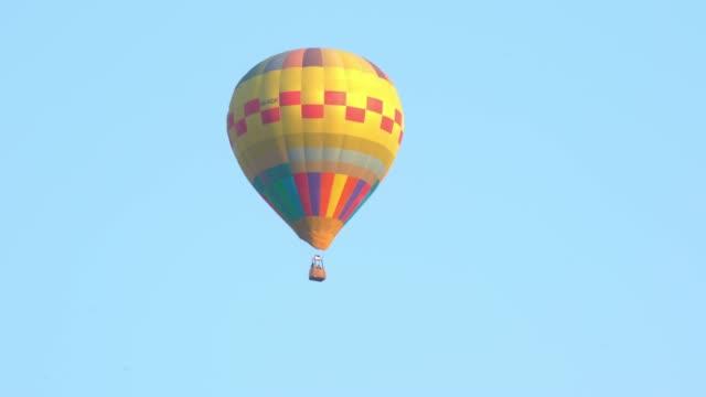 vídeos de stock, filmes e b-roll de o seguimento video de 4k disparou dos únicos balões de ar quente coloridos amarelos que voam acima no vôo do ar da esquerda para a direita no céu branco espectacular e na tela verde ou no fundo chave do chroma. - um único objeto