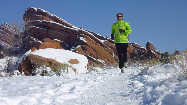 video hd trail runner sulla neve rocce rosse parco colorado - red rock video stock e b–roll