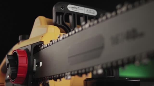 video wiring power tool saw on black background - motosega video stock e b–roll