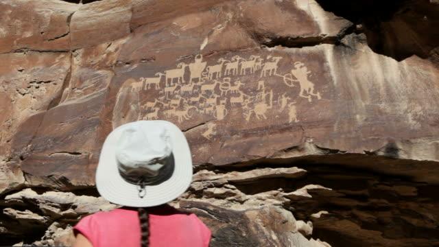 HD video woman inspects hunting scene petroglyphs Utah video
