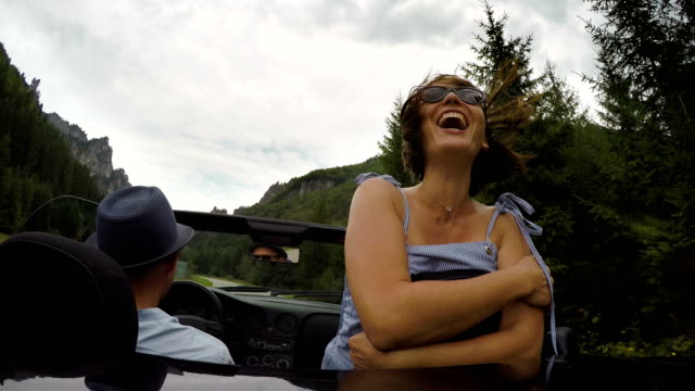 4K video: woman screams from happiness spreading her hands while riding a convertible with her boyfriend video