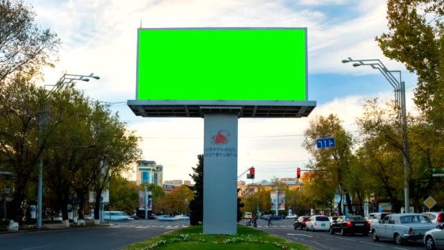 4K TIME LAPSE video.Advertising billboard with green screen with traffic cars and people against the background of the autumn landscape with moving white clouds.Day becomes night.The camera moves away
