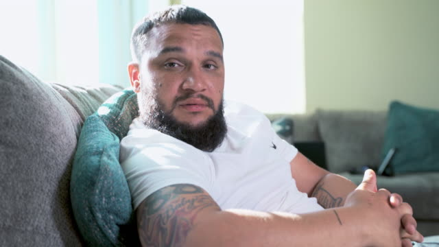 Video-portrait of the handsome bearded man, mixed race with African ancestors, sitting on a couch. - vídeo