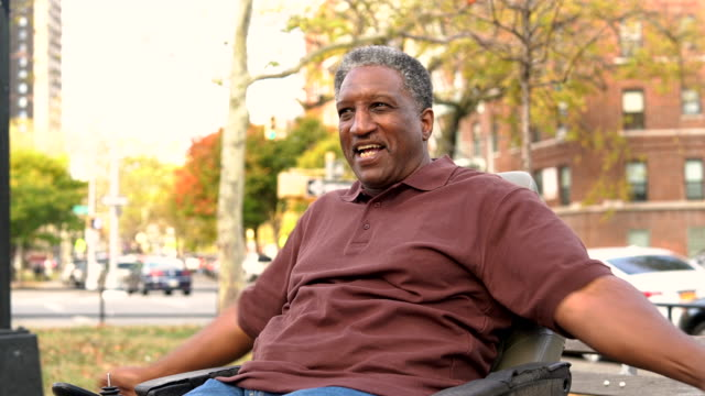 Video-portrait of the positive, optimistic disabled Black man, paralyzed veteran who sitting in wheelchair video