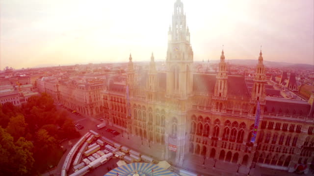 Vienna's beautiful Rathaus City Council building aerial, local government, Europe tourist center, famous tourism attraction, sunset drone fly over, flare in lens, moving aerial camera, Austia capital video