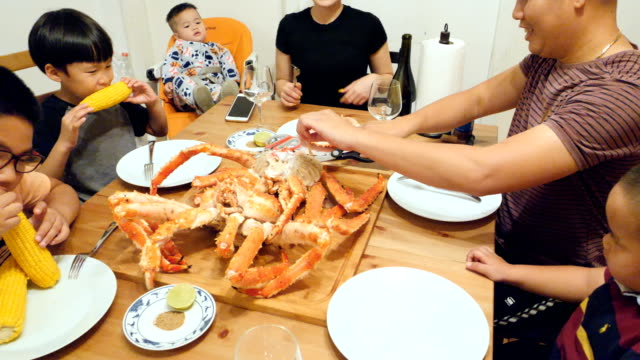 vietnamese family eating a huge crab at home - granchio video stock e b–roll
