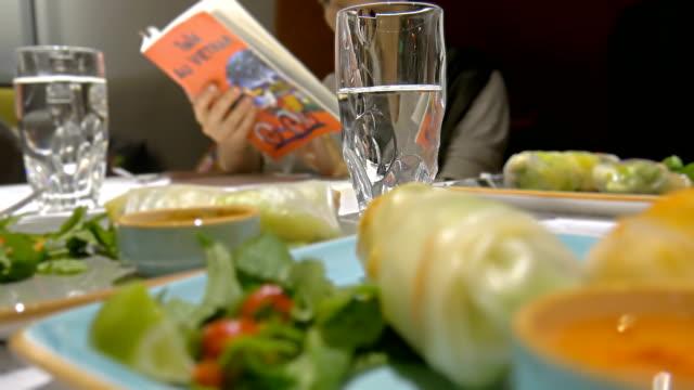stockvideo's en b-roll-footage met vietnamese loempia's met glas water van tafel, vrouwelijke lezen menu - pepernoten
