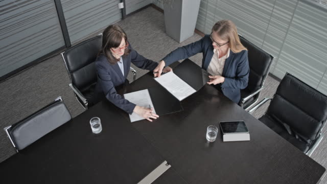 CS View above the table in conference room where two businesswomen are signing a contract and shaking hands video