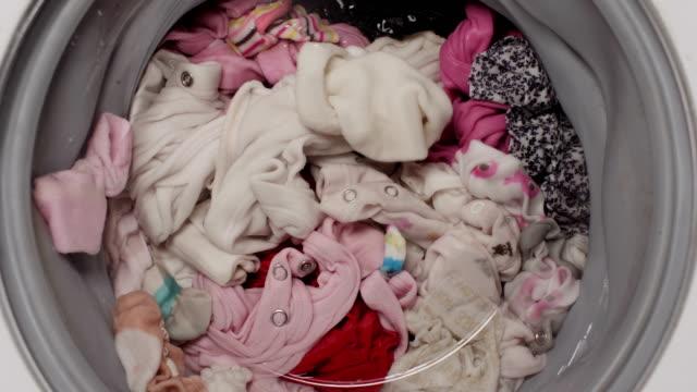 view at kids clothes in washing machine. - pranie filmów i materiałów b-roll