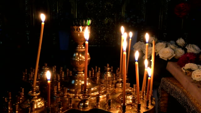 View at the many wax candles burning on altar in dark Orthodox or Catholic cathedral or church. Religion and faith concept Close-up. Indoors.