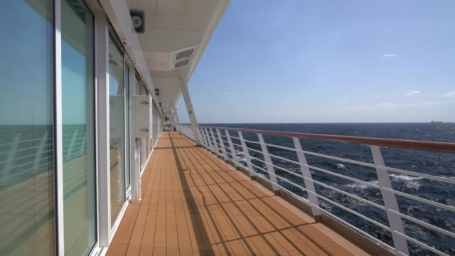 View down the empty walkway on deck of modern cruise ship View down the deck and walkway of a cruise ship crossing the Atlantic railing stock videos & royalty-free footage