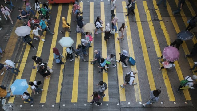 blick hinunter zum crosswalk throng crowdy menschen strömen über die straße in der hauptstunde - überweg warnschild stock-videos und b-roll-filmmaterial