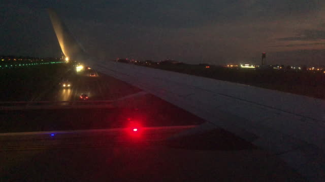 View from a Commercial Airliner Jet Passenger Window of the Wing while Taxiing Down an Airport Runway at Dusk View from a Commercial Airliner Jet Passenger Window of the Wing while Taxiing Down an Airport Runway at Dusk airport runway stock videos & royalty-free footage