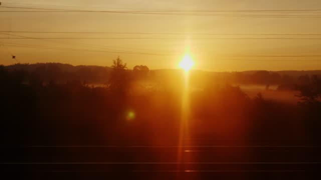 明け方、動いている電車からの眺め。木や建物のシルエット フラッシュ迅速に昇る太陽を背に - 列車点の映像素材/bロール